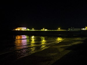 Cromer Pier lit in yellow in support of Marie Curie's National Day of Reflection